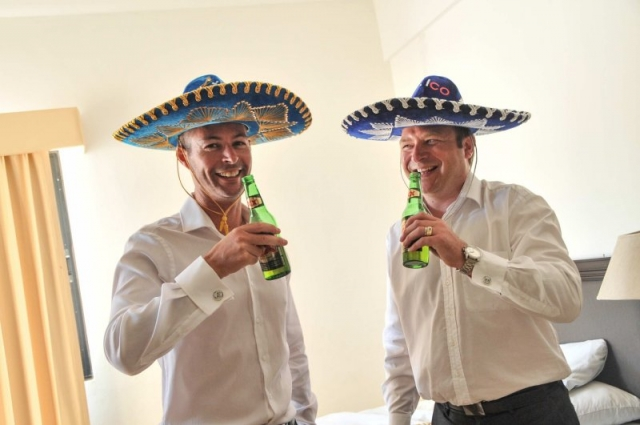Groom and friend in sombreros drinking beer