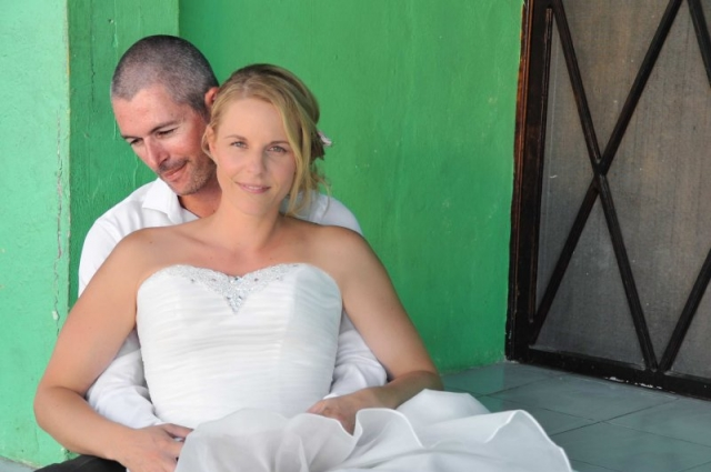 Bride and groom sitting in front of green building
