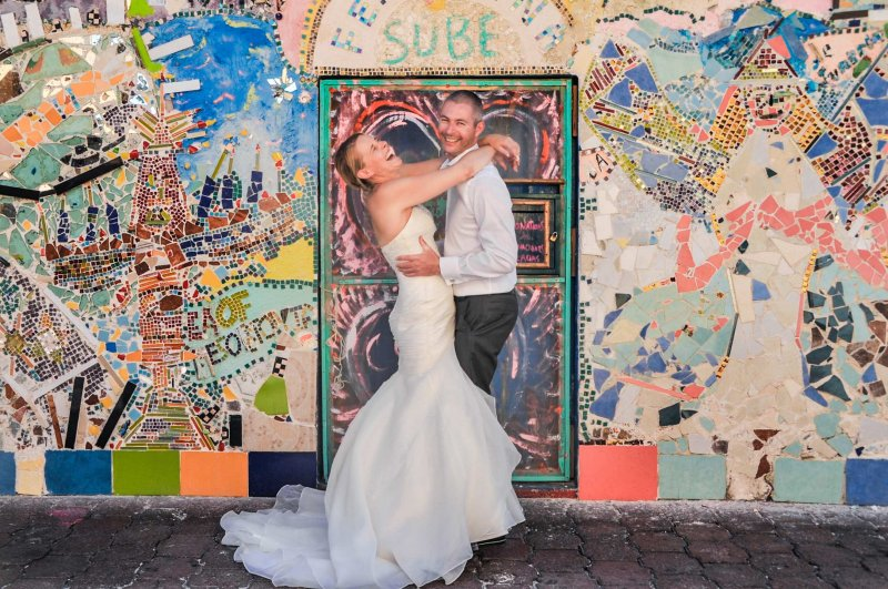 Bride and groom posing in front of building with bright mosiac tile