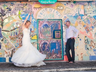 Bride and groom in front of colorful building