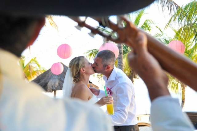 Bride and groom kiss holding cocktails
