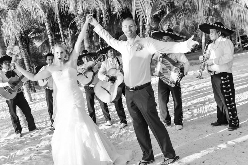 Bride and groom hold hands in air in front of Mexican band