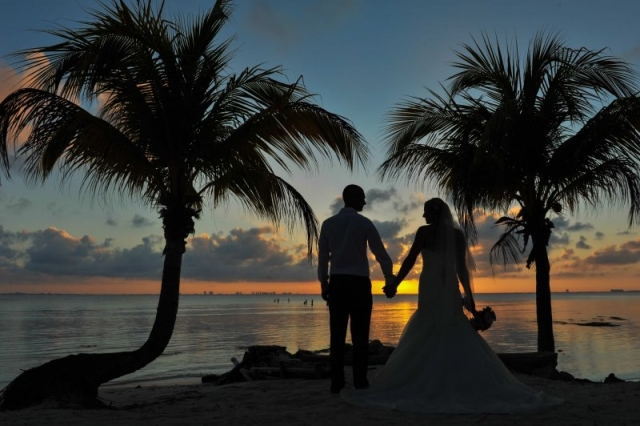 Bride and groom holding hands in silouette at sunset