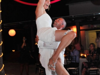 Groom holds bride in air during dance
