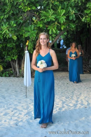 Bridesmaid walking down aisle on beach barefoot