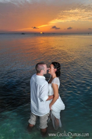Bride and groom wading in the ocean