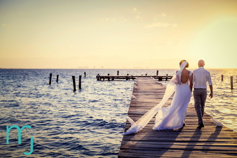 Bride and groom walking down dock at sunset