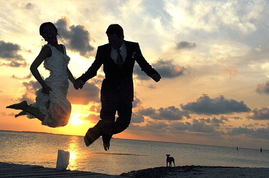 Bride and groom jumping in air at sunset