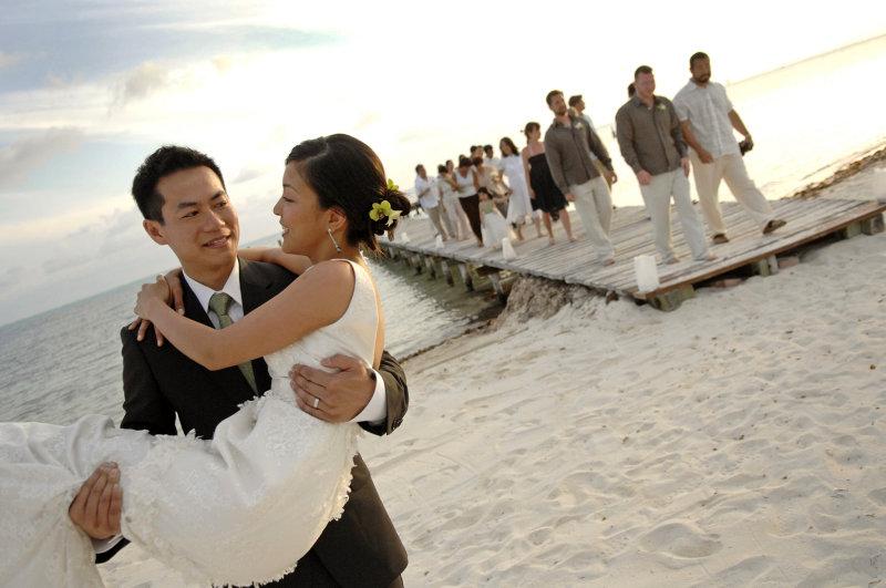 Groom carries bride on beach