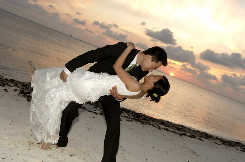 Groom kissing bride on beach at sunset