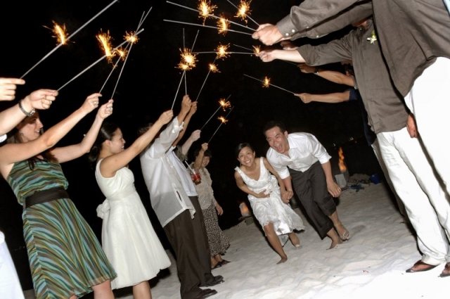 Bride and groom ducking under sparklers held in air by guests