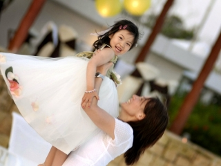 Bride holding up flower girl