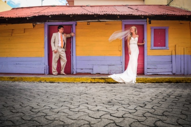 Bride and groom posing in front of colorful building