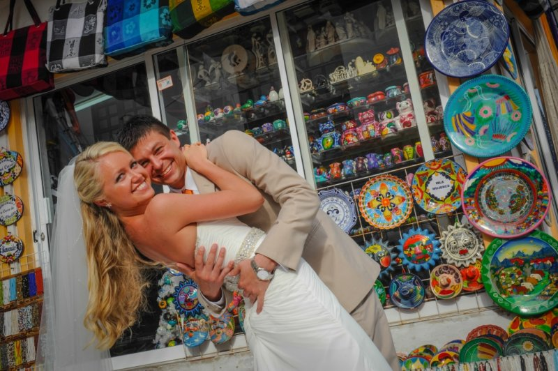 Bride and groom in front of colorful shop