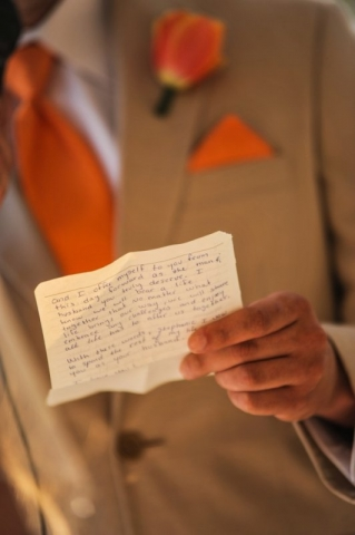 Groom reading from paper during ceremony