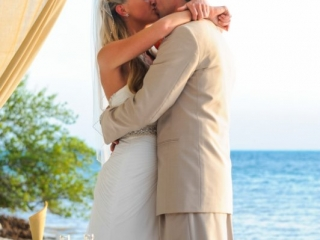 Bride and groom kissing with ocean background