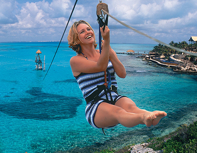 Woman on a zip line above ocean
