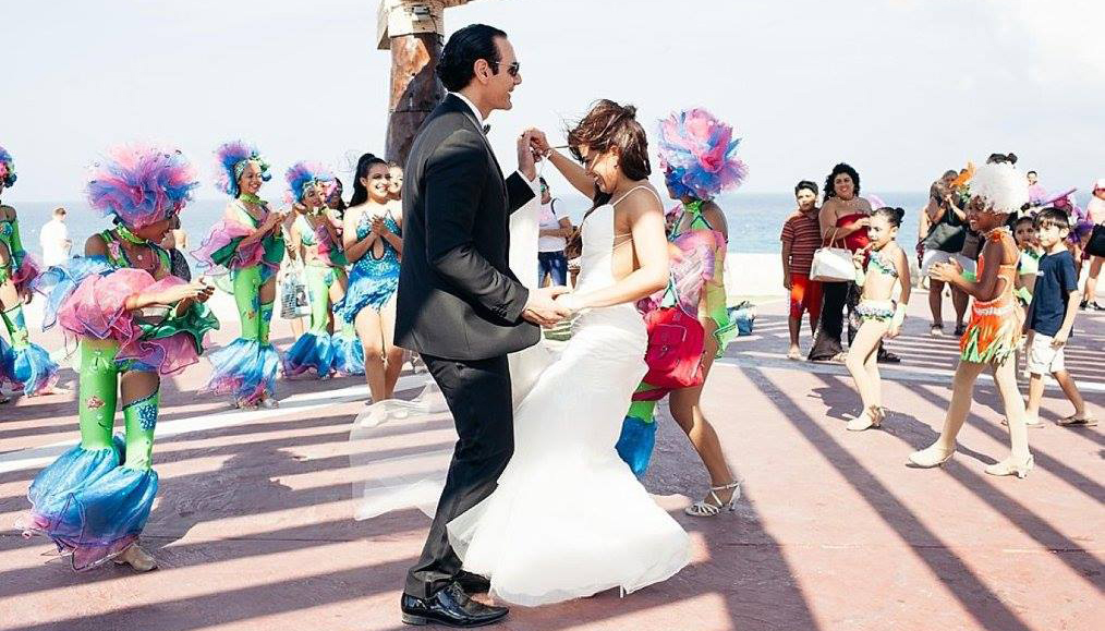Bride and groom dancing with colorful Mexican danceres in background